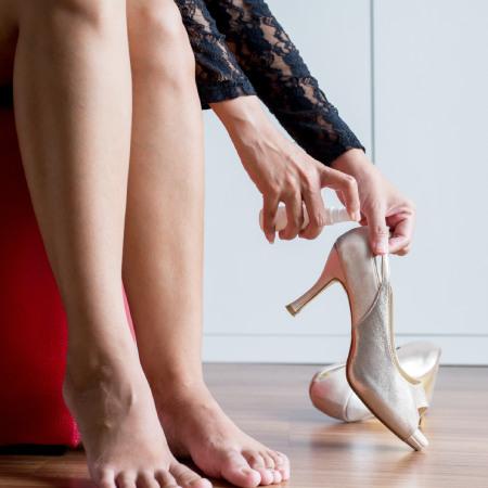 Woman using spray to high heels